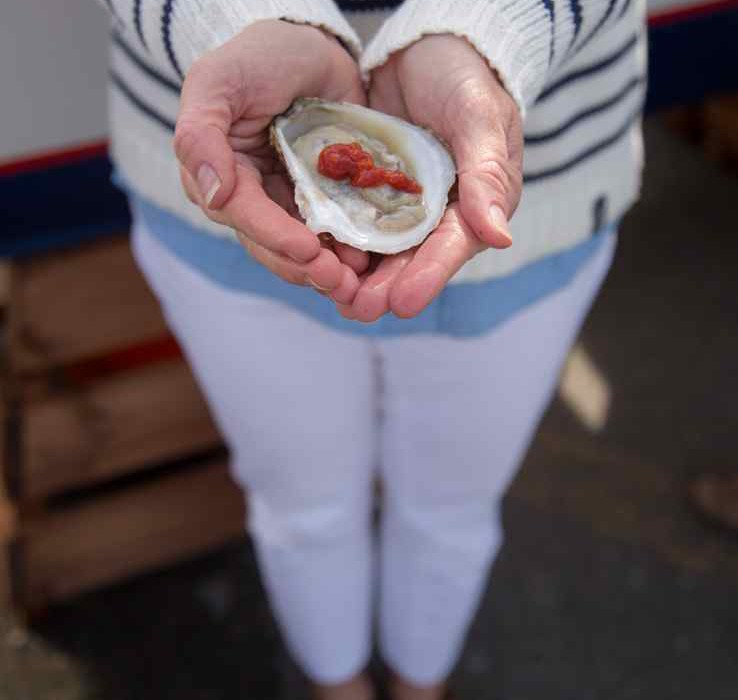woman holding oyster in hand newport ri