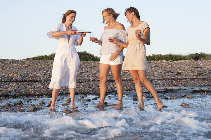 girls pouring drinking rosé wine at the beach